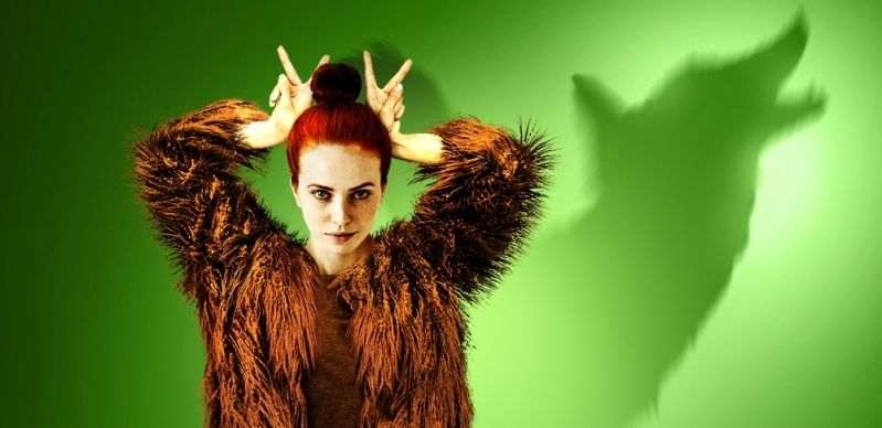 A young woman is dressed in brown fur. In the green background is the silhouette of a wolf.