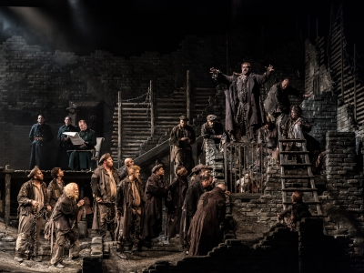 On a grey and atmospheric set, ten men stand chained at the bottom of some steps.