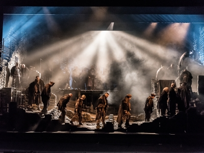 A dozen men wearing dark clothes walk somberly in line, across the dimly lit stage.