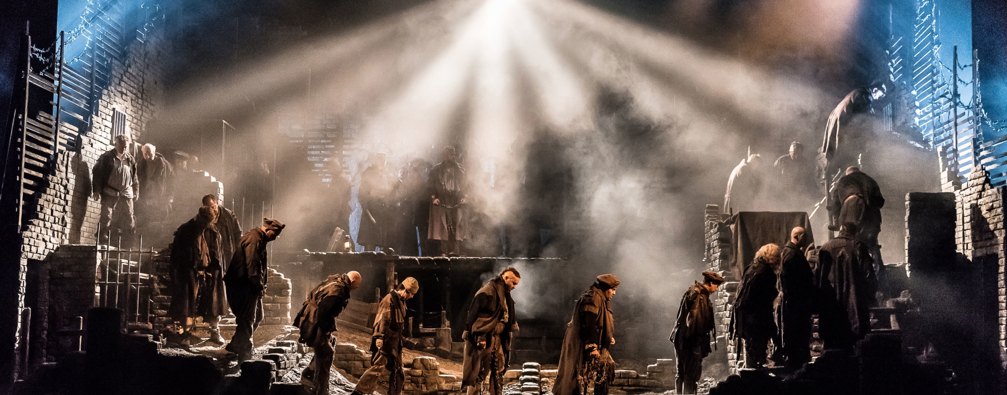 A dozen men wearing dark clothes walk somberly in line, across the dimly lit stage