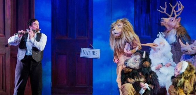A man on the left of the stage plays a flute to a lion, a cow, a bird, a stag, a monkey and a rhino
