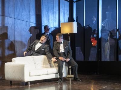 Dark party scene two men singing over white sofa.