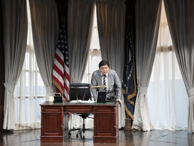 Man leaning on a desk in oval office setting.