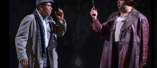 Two men converse dark background, one man holds a gun.