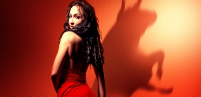 Side view of Carmen, looking over her shoulder at the audience. A silhouette of a bull shows on the red wall.