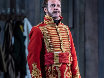 Anatole, dressed in red and gold, looks pensive.