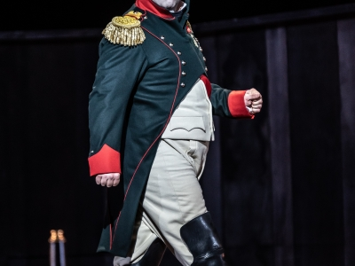Napoleon struts along the stage with a fierce expression on his face.