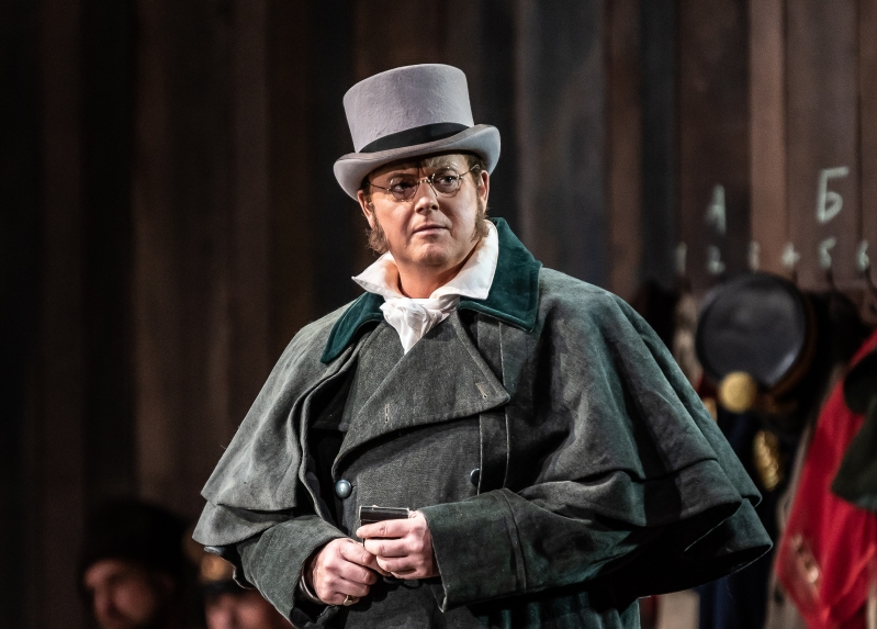 Pierre stands, looking in to the distance. He wears a grey top hat and luxurious-looking robes.