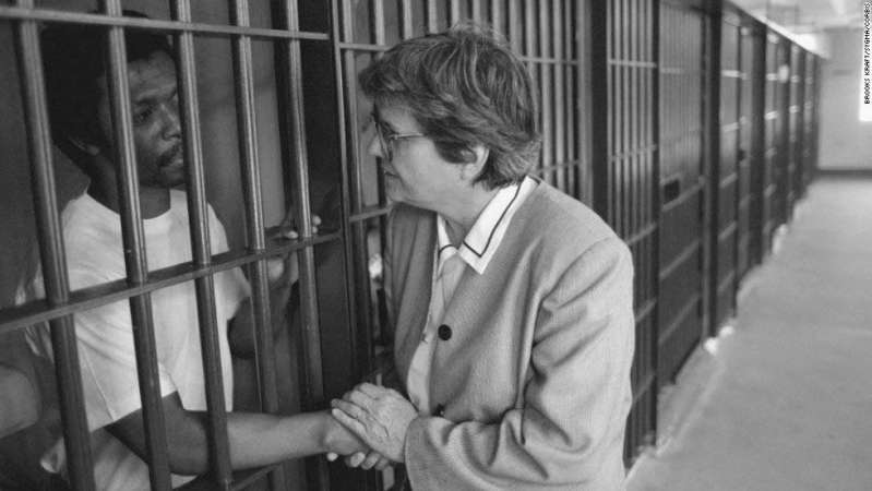 Helen Prejean cups a prisoner's hands through the bars.