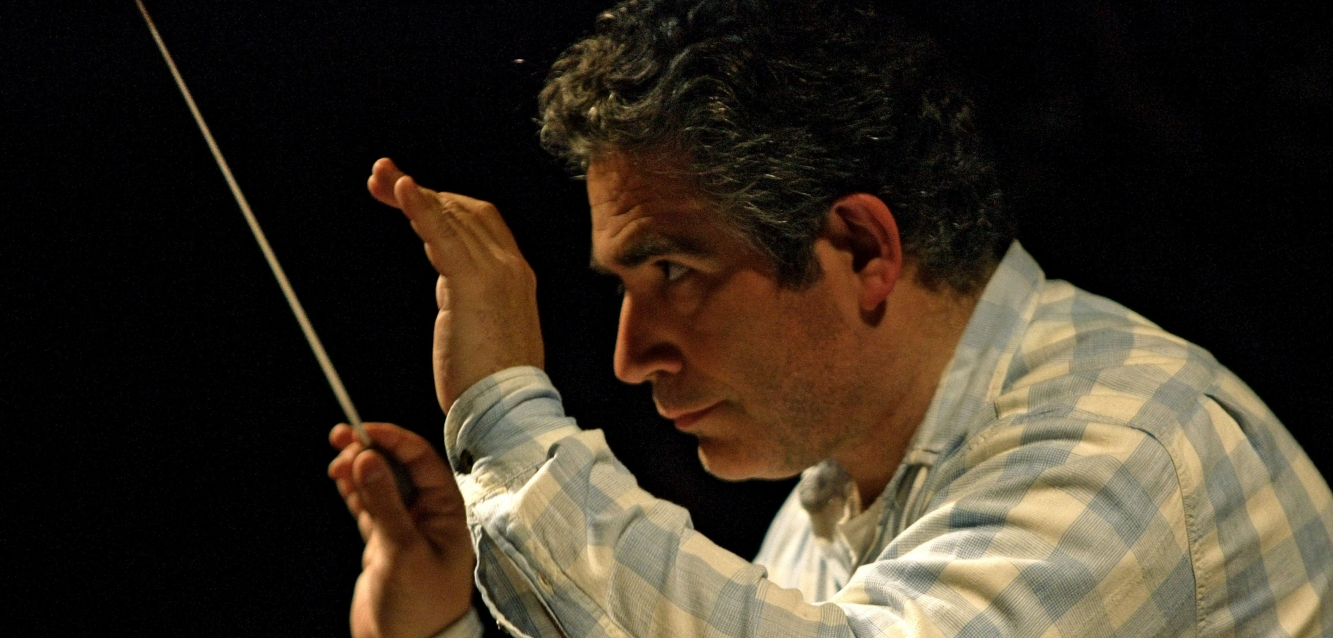 Close up view of Carlo Rizzi conducting. He is wearing a blue and white checked shirt.