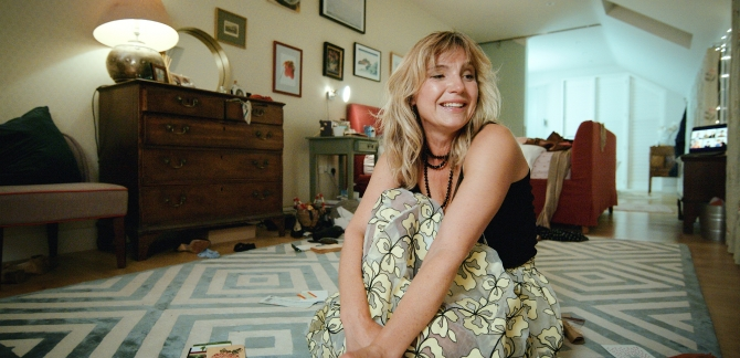 Woman sitting on floor in living room smiling uncomfortably