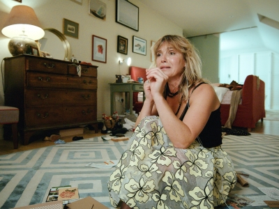 Woman sitting on living room floor crying distraughtly