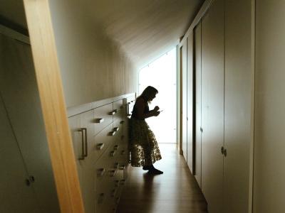 Woman standing in slumped posture between cupboards and wardrobes