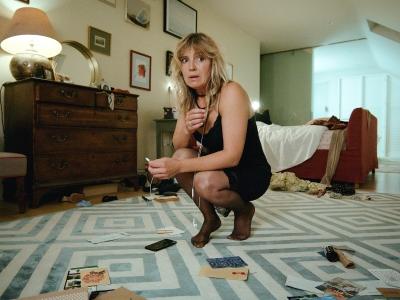 Woman kneeling on living room floor looking alarmed