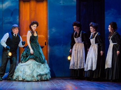Monostatos follows the Queen Of The Night through a yellow door. Three ladies stood in a row bow their heads.