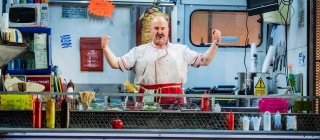 Man in fast food truck looking victorious with arms raised and tensed hands in fists.