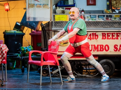 Man in tight red leotard and yellow glasses lunging against chair.