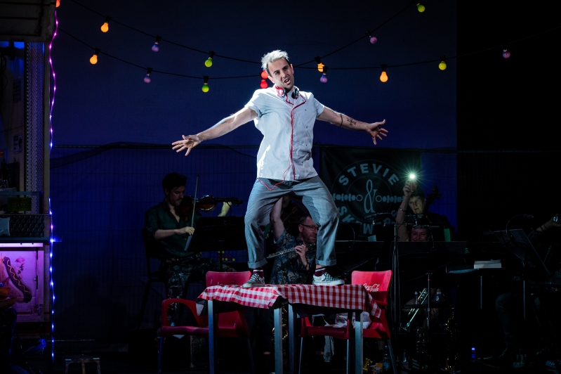 Man in chefs outfit standing on table singing with arms outstretched.