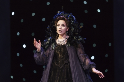 Woman dressed in black with feathered collar sings with one hand in the air.