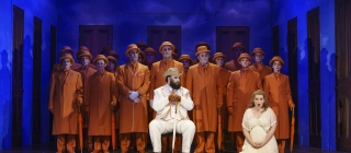 Woman in white kneeling at front, man sat in white, chorus standing in orange behind.