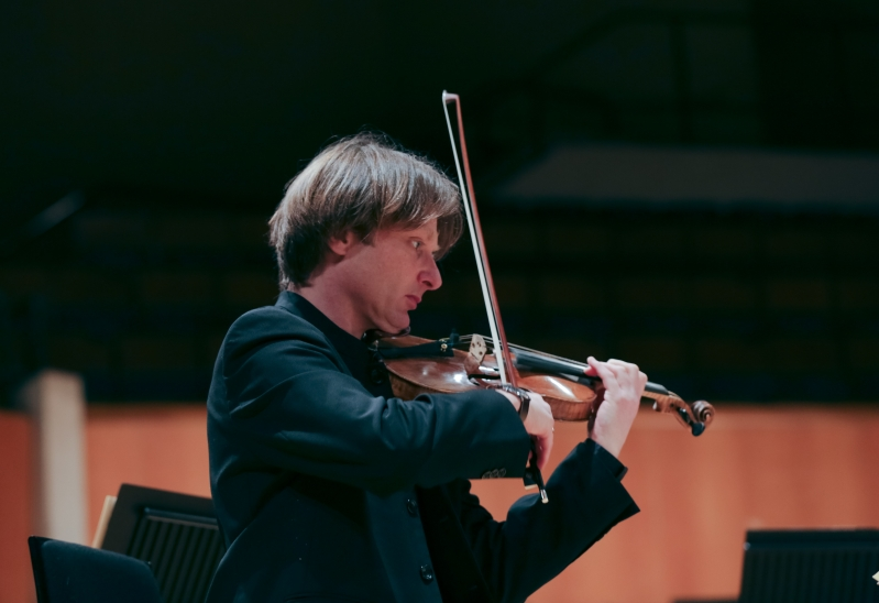 A man in a black jacket plays violin.