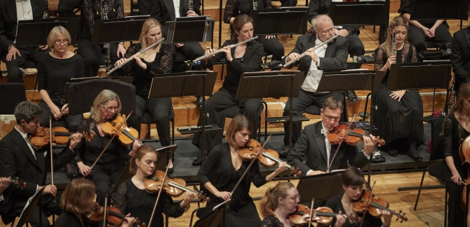 Photo of the orchestra, shows about twenty violinists, flautists and others, sat down.