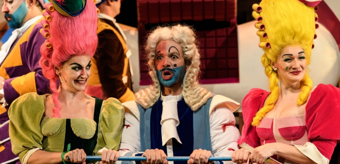 Clorinda and Tisbe, smiling, stand either side of Dandini, who appears surprised.