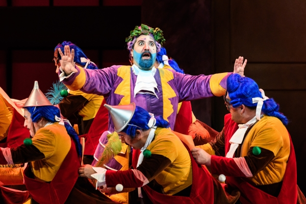 Don Magnifico appears shocked, his hands in the air. He is surrounded by the WNO Chorus, dressed in red, yellow and blue outfits.
