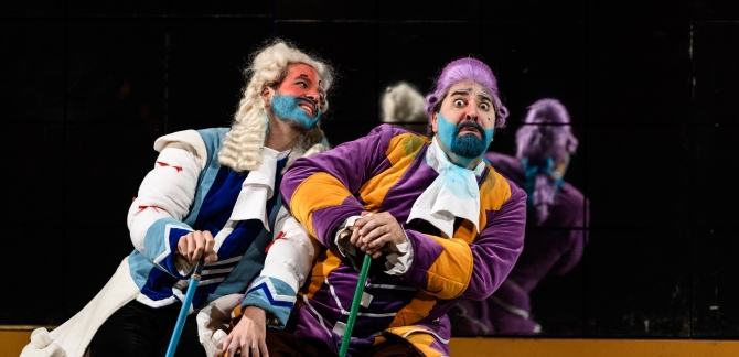 Dandini and Don Magnifico sit side by side in their colourful robes.