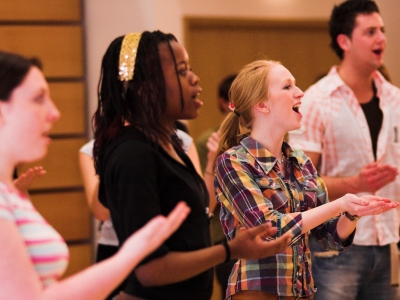 Four young people are singing enthusiastically.