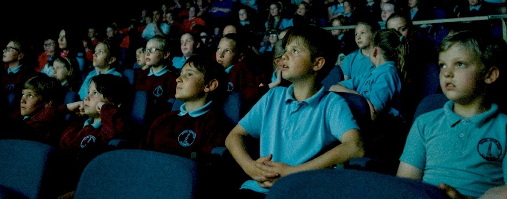 Dark auditorium, audience of school children are watching something unseen on stage or screen