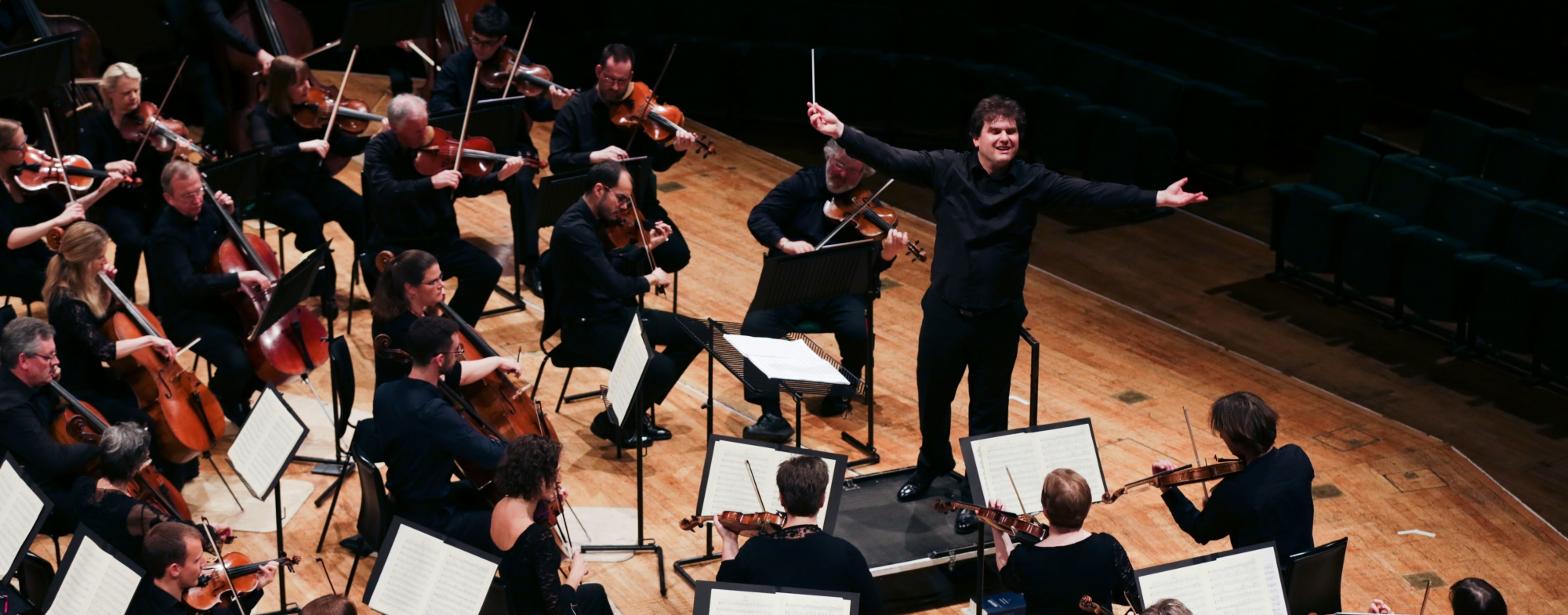 Bird's eye view of the orchestra, with the conductor's arms out wide.