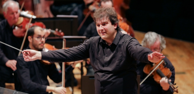 The conductor, Tomas Hanus, side on, holds his arms out wide. There are violin players in the background.