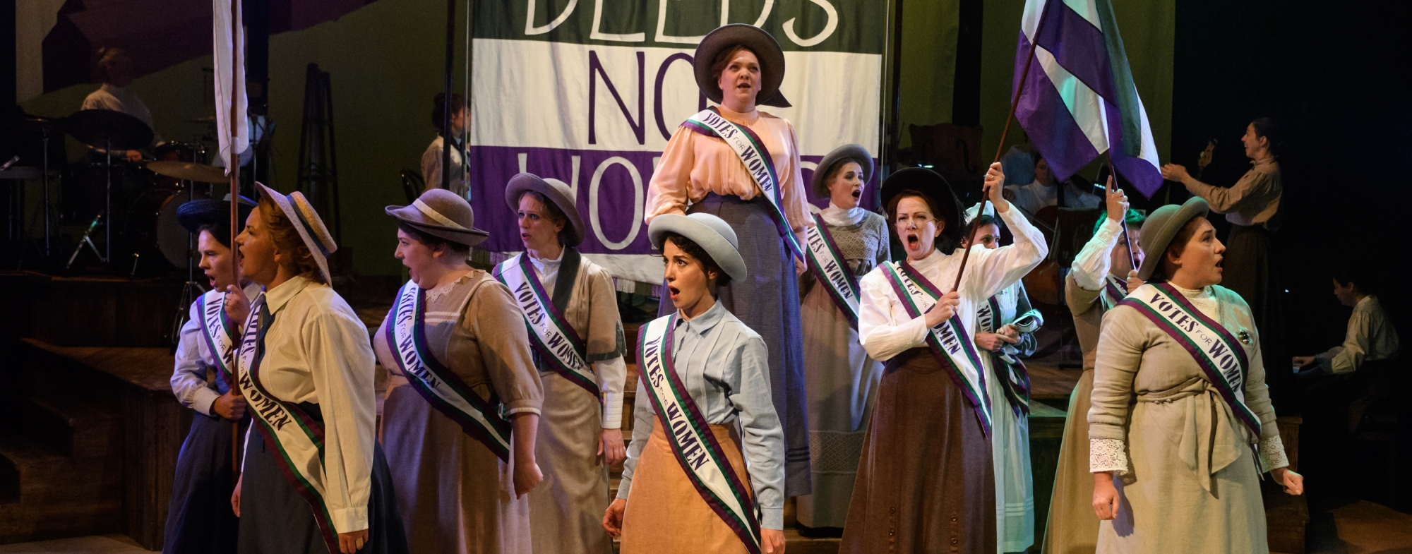 The women's chorus are in traditional dress, marching in front of a green, white and purple 'Deeds Not Words' banner. They are waving green, white and purple flags and wearing Vote for Women Sashes