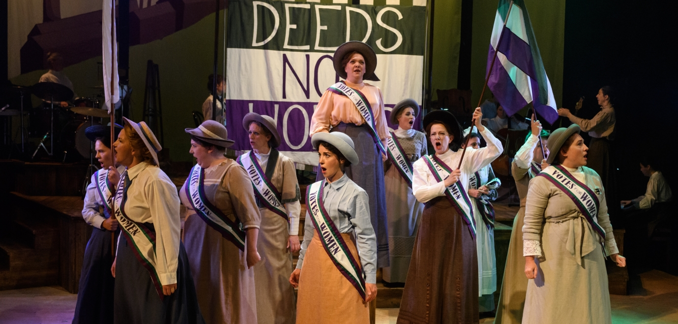 Image shows the women's choru sin traditional dress, marching in front of a green, white and purple Deeds Not Words banner. They are waving green, white and purple flags and wearing Vote for Women Sashes