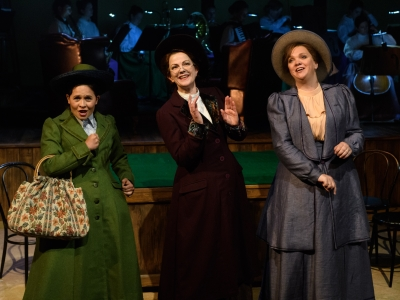 Lottie, Sybil and Lady Rhondda appear jolly, singing to the audience, with the orchestra in the background.