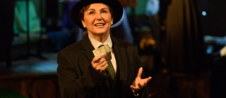 Emcee dressed in a dark blazer, bowler hat and green tie,  hands raised in front of her holding a letter as she sings to to audience, looking slighting upwards.