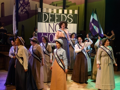 Lady Rhondda is stood up on a stage, surrounded by the women's chorus. They all wear traditional clothes and sashes. They are standing in front of a banner which says 'Deeds Not Words'.