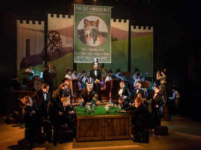 The image shoes a backdrop of a 'Cat and Mouse Poster' with the orchestra in the background.The ladies chorus are sat around a billiard table dressed in suits. They gather around holding cardboard mice with one holding a cardboard cat.