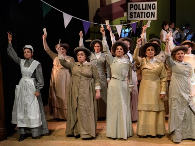 Image shows women's chorus stood at the polling station , all holding their voting cards, and facing the audience.