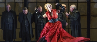 Woman in red dress dances joyfully in front of men in dark suits.