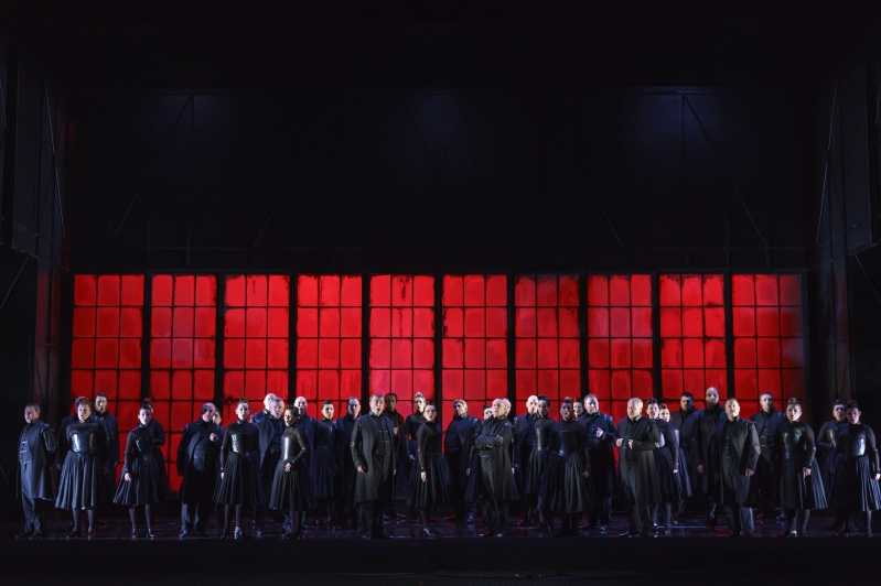 Chorus all dressed in black stood in front of paneled windows lit red.