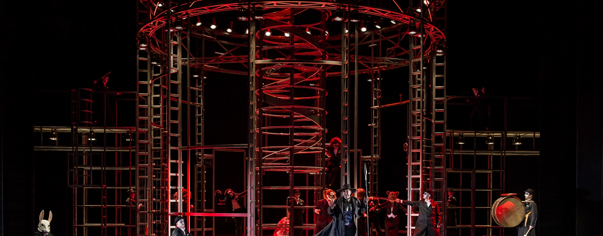 Animals and humans are in an elaborate metal prison cage. The stage is is dimly lit, with red lighting.