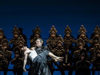 Dancer being held by Guy de Montfort with chorus standing in background