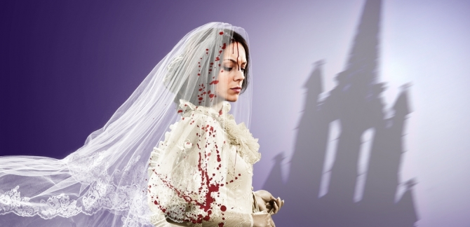 A young woman is dressed in a wedding gown, with the silhouette of a cathedral in the background.