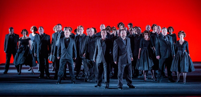 Men and women from the WNO Chorus dressed in grey, with a bright red background.