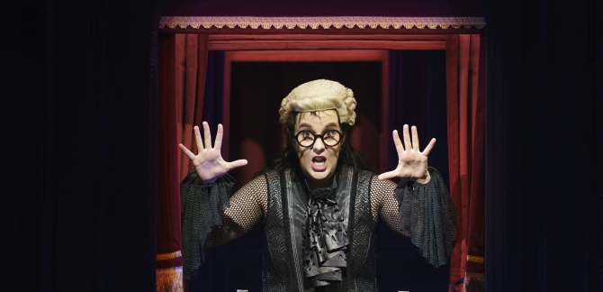 Woman in judges wig and glasses stands in frame with hands raised and outstretched.