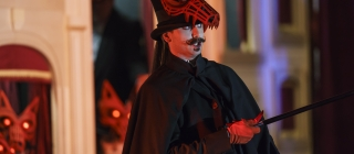 Man in cape and hat with wolf mask with red eyes and moustache points with cane offstage.