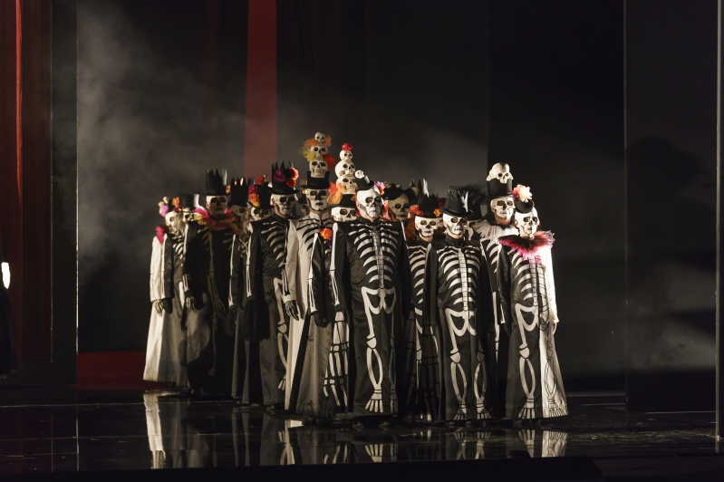 Group dressed in skeleton costumes and face paint form a three wide line.