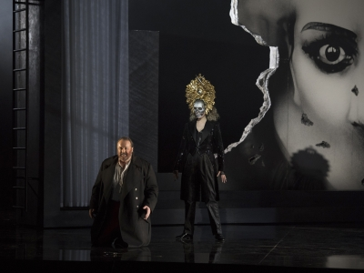 Man kneels front of stage while woman with large gold headdress on stands behind him.